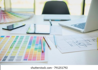 Graphic design and color swatches and pens on a desk. Architectural drawing with work tools and accessories
