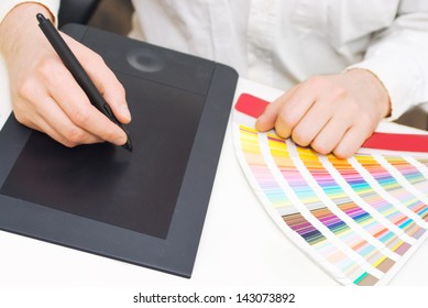 Graphic design, printing, advertising Graphic designer working with digitizer and pantone palette