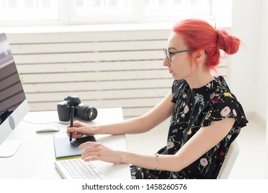 Graphic designer, animator and illustrator concept - young woman with red hair working at the laptop