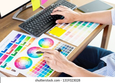 Graphic designer or creative holding Mouse and do his work material color pantone swatch samples art tools at desk in office