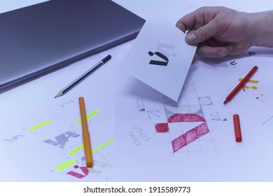 Graphic designer designs a logo against a background of sketches and drawings on a table. Printed logos on paper in a studio with a laptop