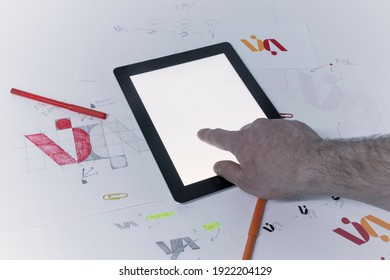 Graphic designer designs a logo against a background of sketches and drawings on a table. Printed logos on paper in a studio with a Tablet