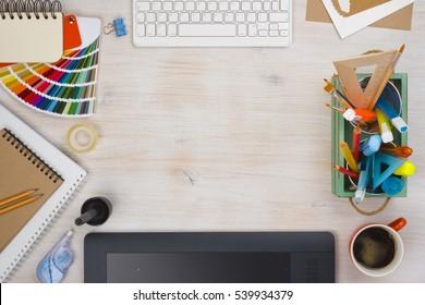 Graphic designer desk essentials top view with wooden texture background.