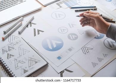 Graphic designer drawing sketch design creative Ideas draft Logo product trademark label brand artwork. Graphic designer studio Concept.