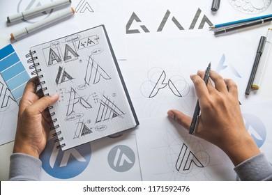 Graphic designer drawing sketch design creative Ideas draft Logo product trademark label brand artwork. Graphic designer studio Concept. - Shutterstock ID 1171592476