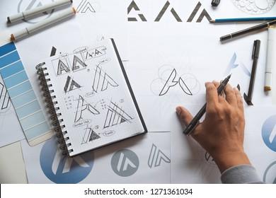 Graphic designer drawing sketch design creative Ideas draft Logo product trademark label brand artwork. Graphic designer studio Concept. - Shutterstock ID 1271361034