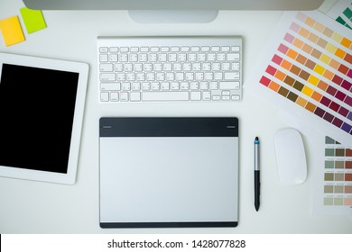 graphic designer with equipment computer, ipad, smartphone and color swatch. Architect using work tools and sample color catalog. business, technology