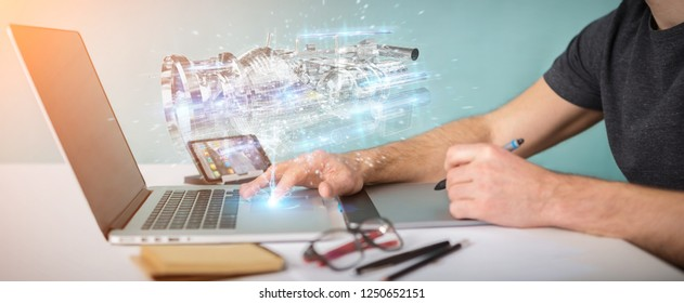 Graphic designer in ofice using wireframe holographic digital projection of an engine