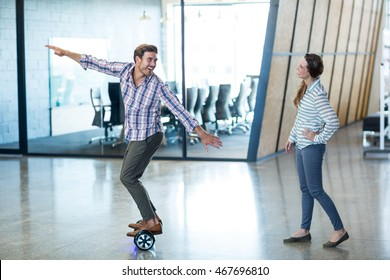 Graphic designer standing on hover board in office