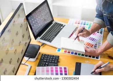 Grafikdesigner-Team, das Web-Design mithilfe von Farbschleifen arbeitet, die mit Tablet-Vorlagen und einem Stift an den Schreibtischen in beschäftigten Kreativbüros