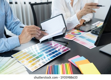 graphic designer team working on web design using color swatches editing artwork using tablet and a stylus at desks In creative office. - Shutterstock ID 1935988633