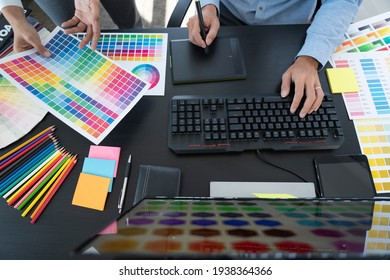 graphic designer team working on web design using color swatches editing artwork using tablet and a stylus at desks In creative office.