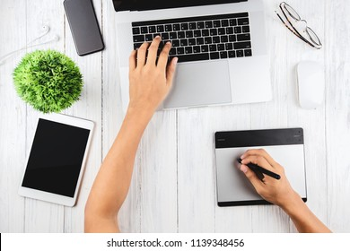 graphic designer using laptop and graphic tablet on top view