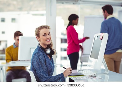 Graphic designer wearing headphones at desk in casual office