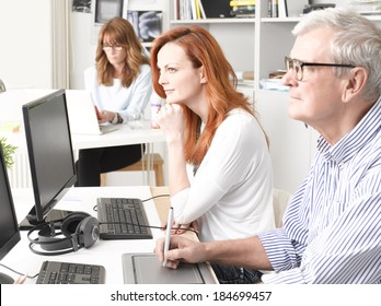 Graphic designer woman sitting at desk and working together with colleagues. Small business.