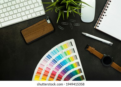 Graphic designer work space with black desk and keyboard, plant, mouse, note pad, smartphone and pen - top view
