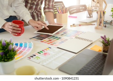 graphic designer working with computer and color swatch. creative man using digital tablet at modern office. Architect using work tools and sample colour catalog.