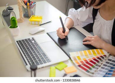 graphic designer working with computer and color swatch. creative woman using digital tablet at modern office. Architect using work tools and sample colour catalog.