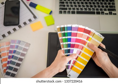 graphic designer working with computer and color swatch. creative woman using digital tablet at modern office. Architect using work tools and sample colour catalog