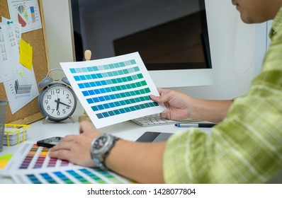 graphic designer working with computer, ipad, smartphone and color swatch. creative man using stylus pen and digital tablet at modern office. Architect using work tools and sample colour catalog.