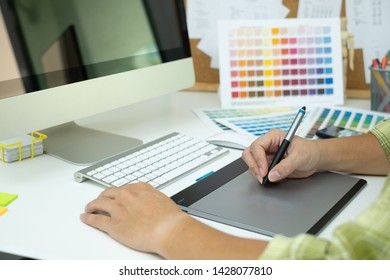 graphic designer working with computer, ipad, smartphone and color swatch. creative man using stylus pen and digital tablet at modern office. Architect using work tools and sample color catalog.