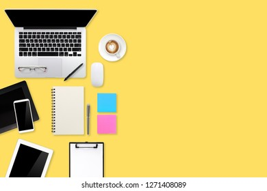 graphic designer working desk top view with laptop computer, pen display, tablet stylus, office supplies and coffee cup on yellow pastel background
