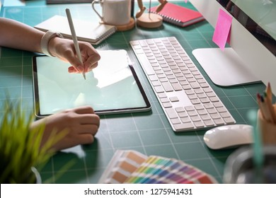 Graphic designer working with digital drawing tablet at her office