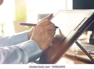 Graphic Designer working with digital Drawing tablet and Pen on a computer. Smooth tracking shot with nice backlit lensflare.