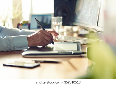 Graphic Designer working with interactive pen display, digital Drawing tablet and Pen on a computer. Smooth tracking shot with nice backlit lensflare.