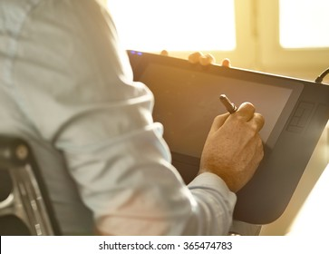 Graphic Designer working with interactive pen display, digital Drawing tablet and Pen on a computer. Backlight shot with lensflare