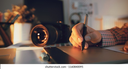 Graphic designer working on digital tablet. Camera on desk in background. Photographer working at office.