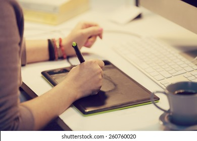 a graphic designer is working and using a graphic tablet