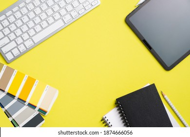 Graphic designer workspace top view with tablet, computer keyboard, RAL color palette, notebook on yellow background. Flat lay, overhead. Creative professional office desk.