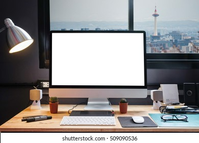 Graphic designer's workspace equipped with a pen tablet, a computer and white screen for text with beautiful Kyoto Tower in Japan  from the window