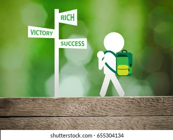 graphic image of backpacker stand next to success sign on wooden ground over nature blur background, business concept