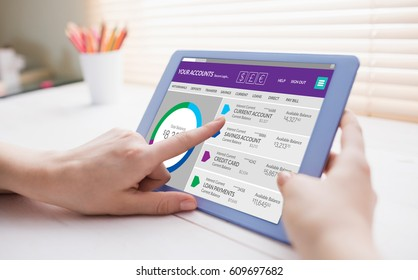 Graphic image of bank account web site against cropped image of person using on digital tablet
