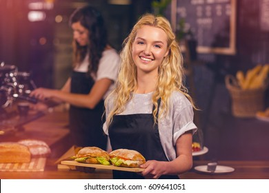 Graphic image of flare against portrait of pretty waitress holding tray with sandwiches