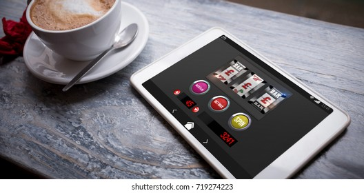 Graphic image of slot machine on mobile display against cappuccino and digital tablet on table
