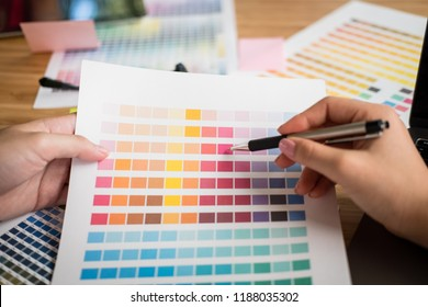 graphic or interior designer choosing color from swatch sample or catalogue palette guide at workplace. artist discussing design & idea at office. business people brainstorming for new creativity