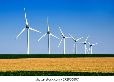 Graphic modern landscape of wind turbines aligned in a green and yellow field