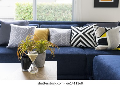 graphic pattern cushion on blue sofa with plant pot on table