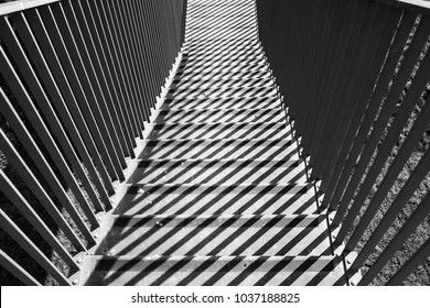 Graphic shapes - parallel shadow lines on stairs. Black and white, sun and shadow plays. High contrast.
