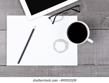 Graphic tablet with glasses paper sheet and coffeeon office desk
