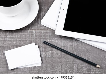 Graphic tablet with pencil paper cards and coffee on office desk