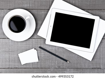 Graphic tablet with pencil paper sheet and coffee on office desk