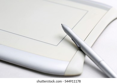 graphic tablet and pressure sensitive pen on white background