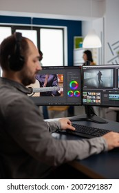 Graphic video production working on pc with two displays editing video and audio footage sitting in creative workplace. Video maker employee processing film montage in digital multimedia company