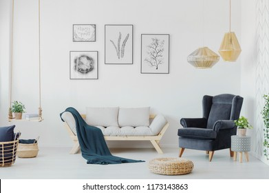 Graphics above a wooden couch with pillows, armchair and swing with a plant in a creative living room interior. Real photo