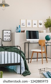 Graphics in frame on the empty grey wall of trendy bedroom interior with single metal bed and workspace with all in one computer