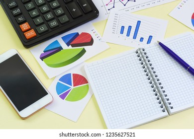 Graphics, notebook, pen, calculator and phone lie on a yellow background. Analytical business still life